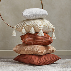 Stacked cushions on a carpet with different textures in neutral and rust tones