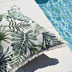 Tropical outdoor cushion with a fringe next to a swimming pool