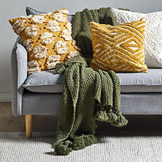 Patterned cushions in an mustard colour on a two seater sofa