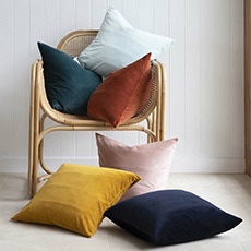 Solid, plain cushions stacked onto a rattan chair