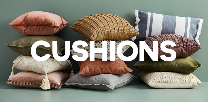 Various cushions stacked up, including velvet, textured, linen, tassel and fabric cushions on a green background