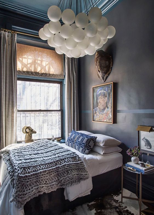 Here drama comes courtesy of the modern lighting cluster in a period space and a dark wall behind the bed. Image – Matthew Williams.