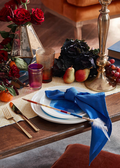 Pops of blue on the table draw the eye in and keep the warm colours from taking over. Photography Denise Braki, Styling Allira Bell.